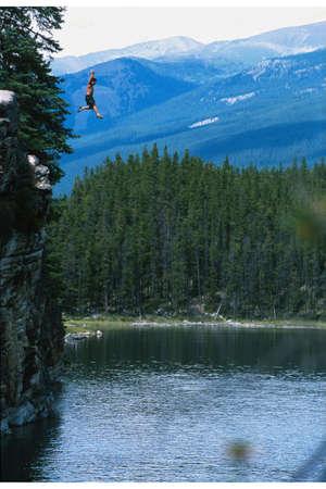 corey hochachka: Man jumping off cliff into lake
