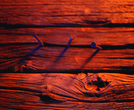 corey hochachka: Three nails in wood in red tones