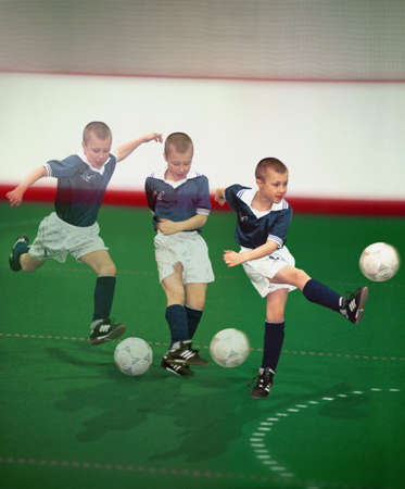 indoors: Multiple exposure of boy kicking soccer ball