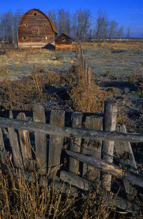 Wooden fence with old barn in background photo