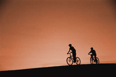 Silhouette of cyclists on hill Stock Photo - 5493637