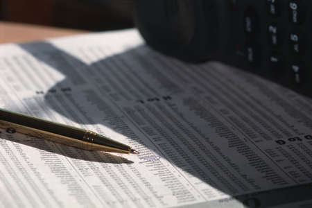 corey hochachka: Closeup of pen and circled Investment in newspaper