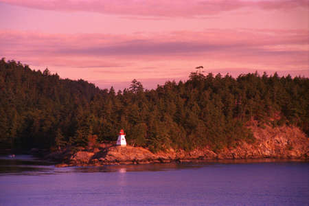 corey hochachka: Small lighthouse with trees and hill behind