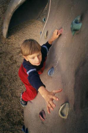 Young boy ascending climbing wall