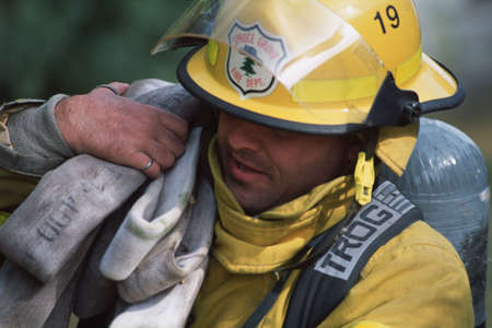 corey hochachka: Fireman carrying hose Stock Photo