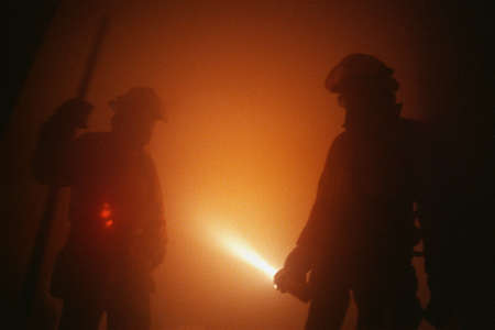 Firemen in smoky room spraying water from hose photo