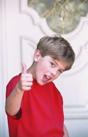 carson ganci: Boy with thumbs-up in front of door