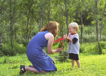 carson ganci: Mother and son with flowers in park Stock Photo