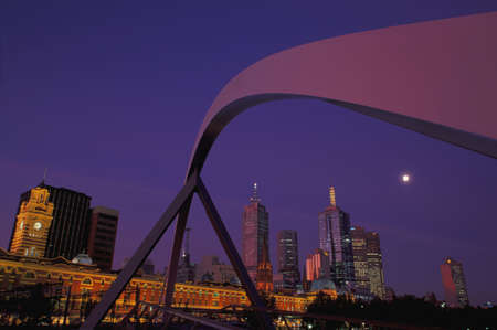 carson ganci: Curved span of bridge with city skyline in background