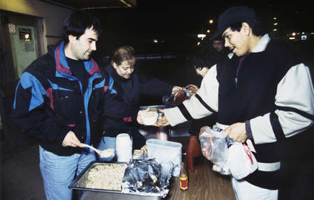 goodwill: Volunteers and homeless at soup kitchen Stock Photo