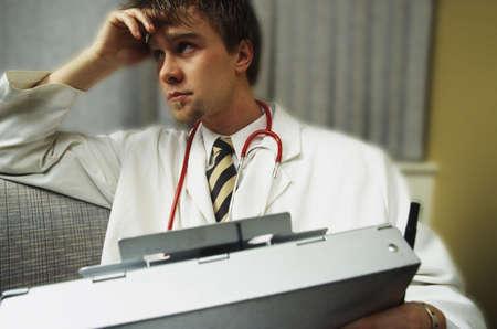 estudiantes medicina: Doctor en sof� con cuaderno de pacientes de la historia