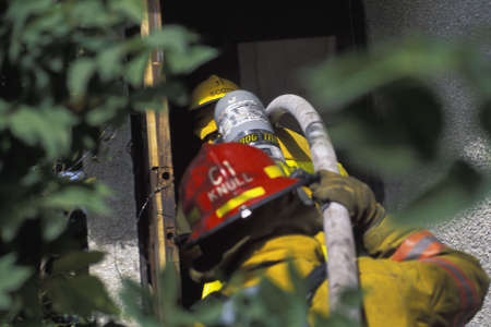 Fireman pulling hose to building