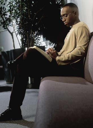 leyendo la biblia: Hombre de lectura en sof�