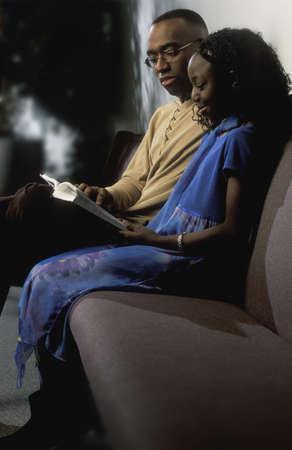 hymnal: Uomo e ragazza lettura libro sul divano