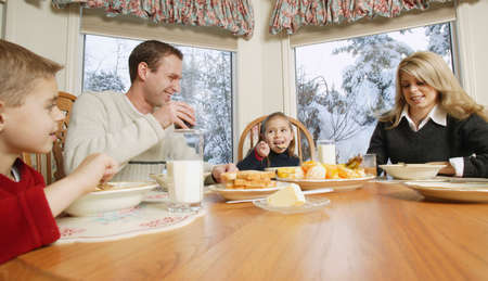 Family smiles at breakfast table photo