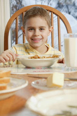 darren greenwood: Young boy eating cereal at breakfast table