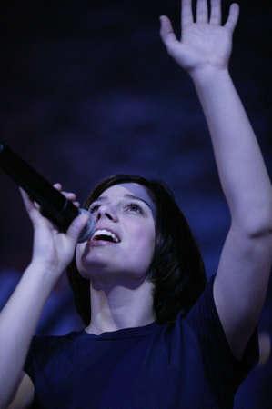 Woman raising hand in worship Stock Photo