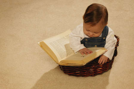 Baby reading a book in a basket Stock Photo
