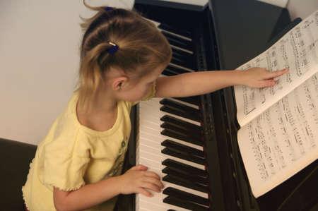 Kind leert piano spelen Stockfoto