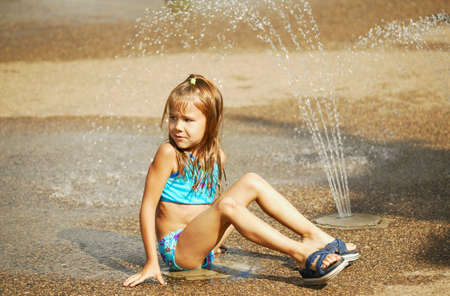wet suit: Child sits beside sprinkler Stock Photo