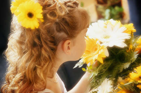 smells: Flower girl smells bouquet Stock Photo