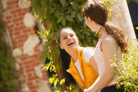 Two girls share a joke
