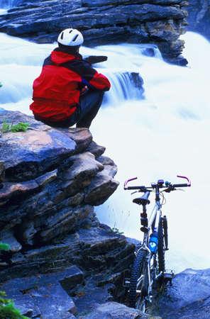 Cyclist taking a break at small waterfalls Stock Photo - 6213566