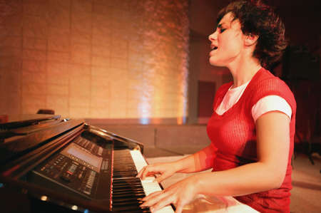 Woman plays the piano and sings photo