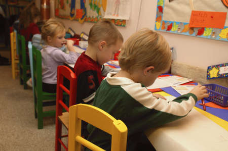 carson ganci: Many childern drawing pictures in a kindergarten class Stock Photo