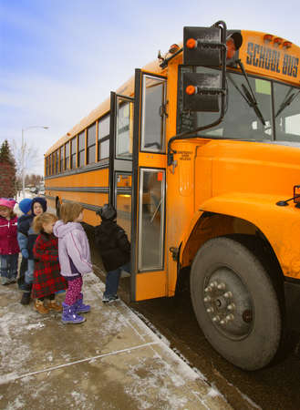 Elementary schoolchildren boarding school bus on a cold winter day in Edmonton, Alberta, Canada