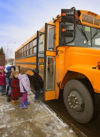 Elementary schoolchildren boarding school bus on a cold winter day in Edmonton, Alberta, Canada Фото со стока - 6213664