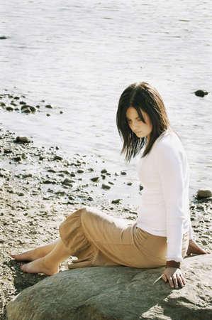 fixate: Woman sits on beach