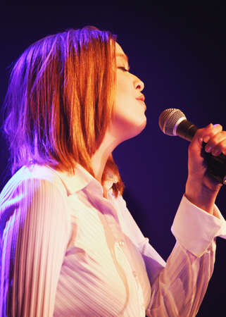 A woman sings into a microphone Stock Photo