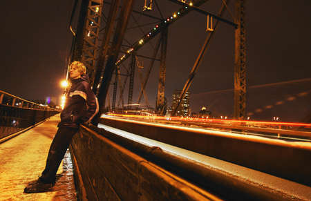 imaginor: Man sits on side of bridge Stock Photo
