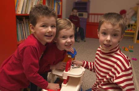 carson ganci: Three boys playing together at preschool Stock Photo
