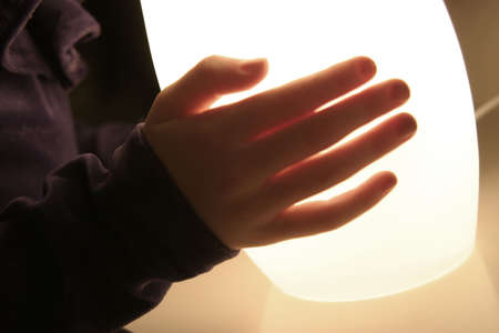 discover: A hand touching a lamp Stock Photo