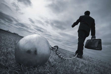 鉄球と鎖を持ったビジネスマン 写真素材