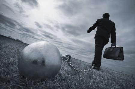 schuld: Zaken man met een bal en ketting  Stockfoto