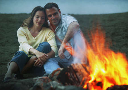 campfires: Couple keep warm by campfire