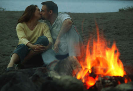 darren: Couple embrace by campfire Stock Photo