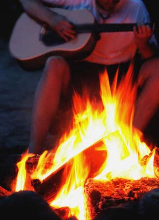 darren: Playing guitar by a bonfire Stock Photo