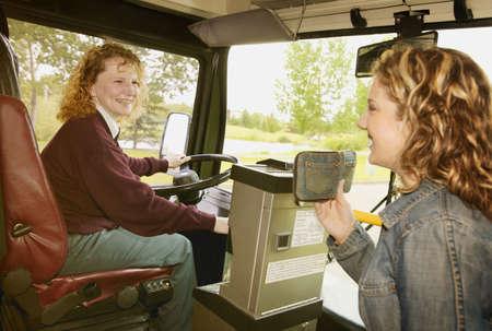 Woman boards a public bus Stock Photo