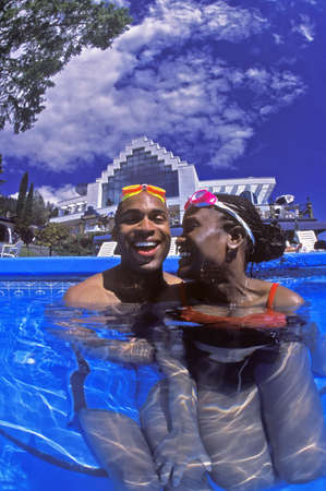 Portrait of Happy Couple in swimming pool photo