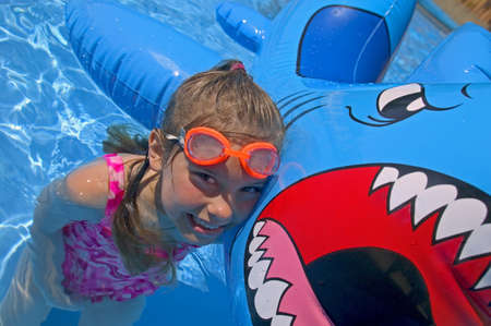 Girl playing in swimming pool with inflatable shark