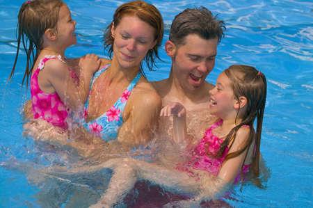 スイミング プールで幸せな家族の肖像画