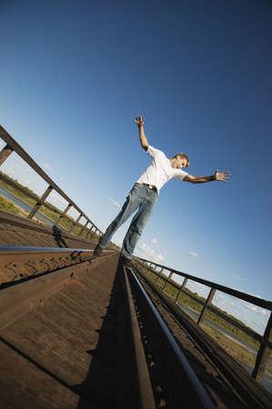 Teen walks on train tracks