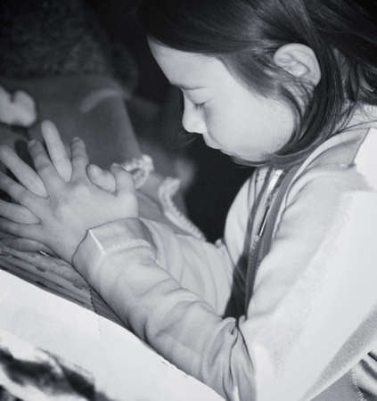 Girl kneeling and praying by bed photo
