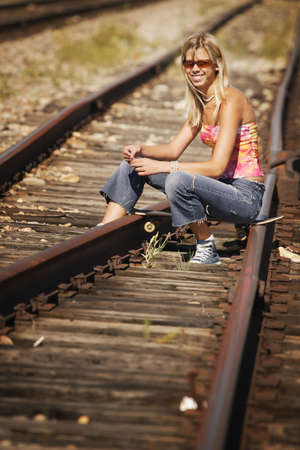 Woman sitting on train tracks photo