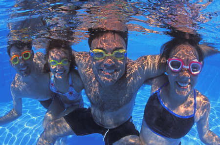 girl swimming: Family group in swimming pool