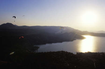 peace risk: Para gliders in flight over lake